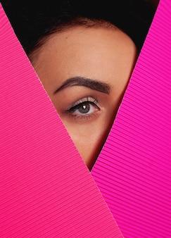 분홍색 종이 통해 찾고 메이크업을 가진 여자입니다. 한쪽 눈과 눈썹이 보입니다. 회색 눈이 가까이