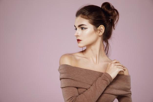 Женщина с макияжем позирует в профиль на розовом