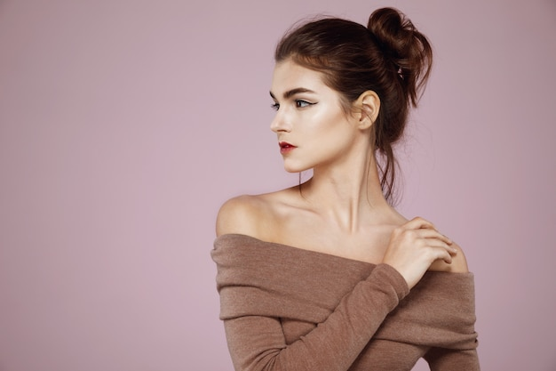 Woman with makeup posing in profile on pink