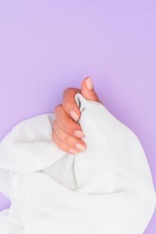 コピースペースの白い布を持って行われたマニキュアの女性
