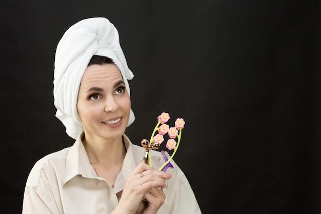 シャツとタオルで頭に手動マッサージャーを持っている女性