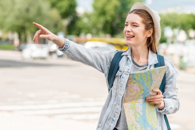 空気正面で彼女の指を指しているマップを持つ女性