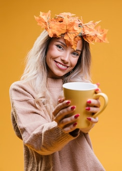 Woman with maple leaves tiara showing cup of coffee standing against yellow wall