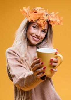 Женщина с кленовыми листьями тиара, показывая чашку кофе, стоя у желтой стены