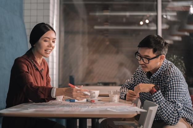 Женщина с маркером. женщина держит маркер, делясь своими идеями о новом проекте со своим деловым партнером