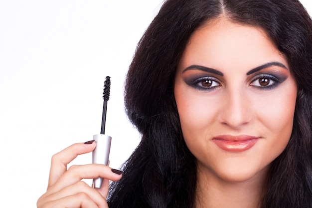 Woman with mascara brush in hand