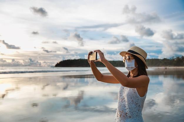 Женщина с маской и мобильным телефоном