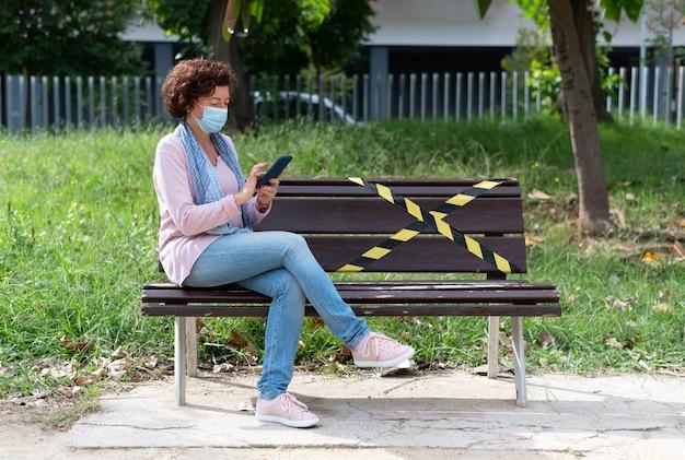 社会的距離のために予約されたスペースのあるベンチに座っている、マスクと携帯を持った女性。新しい現実