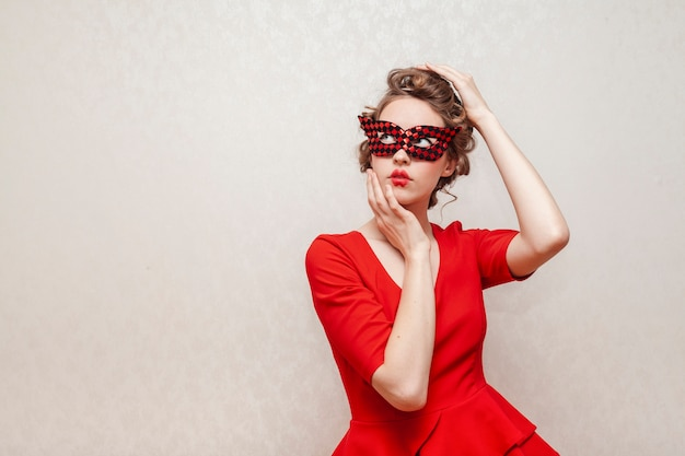 マスクと赤いドレスのポーズを持つ女性
