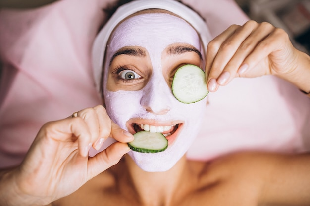 Woman with mask and cucumber on her eyes