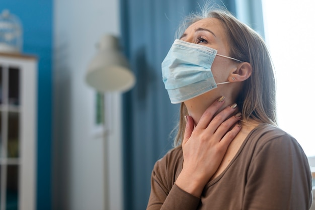 Woman with mask having problems with her throat