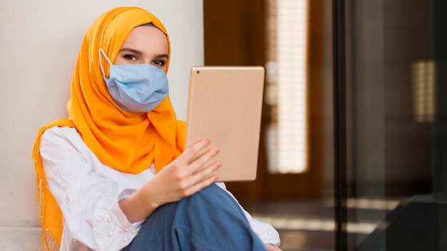 Woman with mask holding tablet