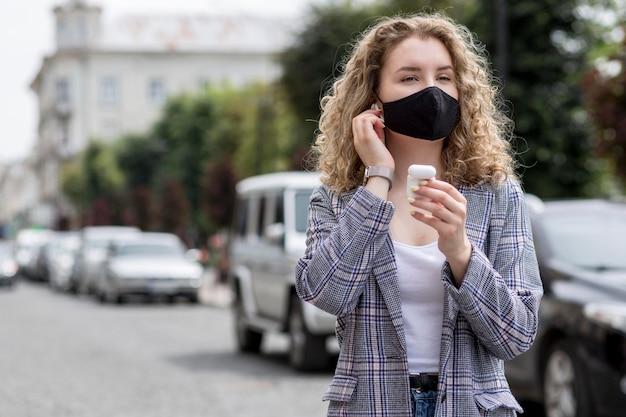Airpodsと屋外のマスクを持つ女性