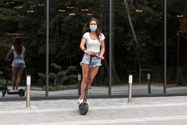 Woman with mask riding an electric scooter