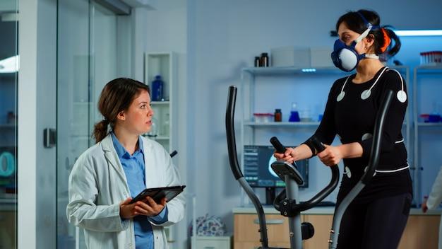 電極を使用して心拍数をテストするクロストレーナーで実行されているマスクを持つ女性、タブレットにekg結果を書いている医学研究者。科学スポーツラボで身体的持久力を監視するパフォーマンスアスリート