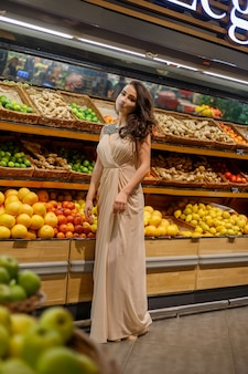 Woman with mask safely shopping groceries amid the coronavirus pandemic in stocked grocery store. brunette buy fruits, vegetables at supermarket. shortage fresh produce. woman evening sparkling dress