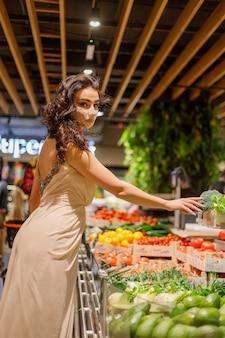 코로나 바이러스 전염병 속에서 안전하게 식료품을 쇼핑하는 마스크를 쓴 여성