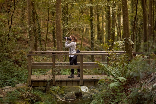 Woman with mask taking photos on a bridge in a forest
