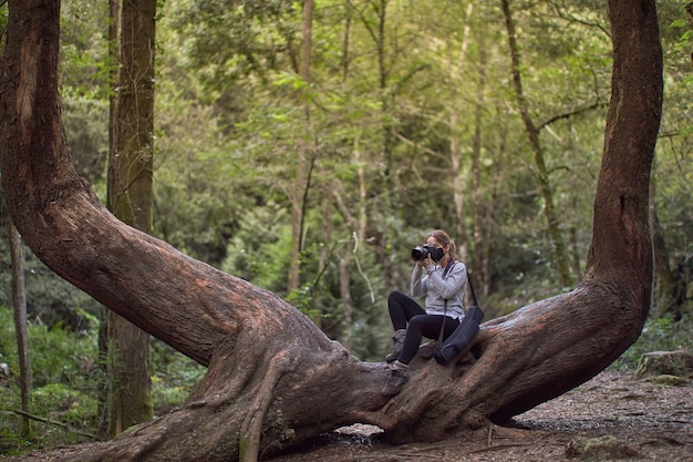 Woman with mask taking photos on a tree trunk