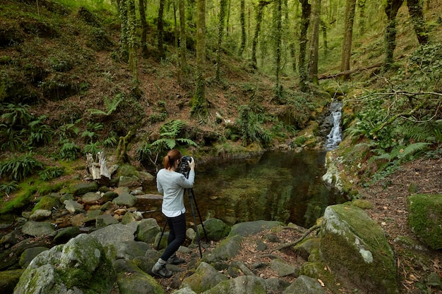 Woman with mask taking photos of waterfall