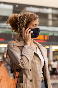Женщина с маской разговаривает по телефону