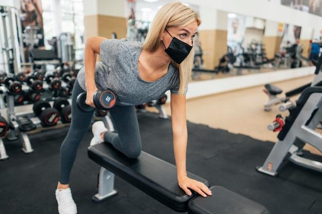 Женщина с маской тренировки в тренажерном зале