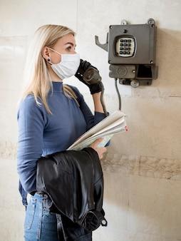 電話を使用してマスクを持つ女性