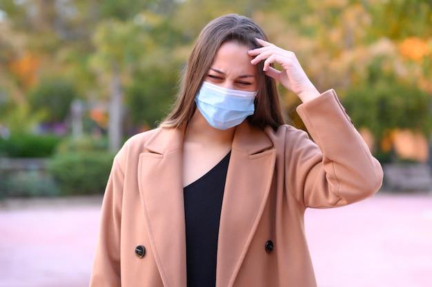 Женщина с маской с головной болью на улице