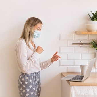Woman with mask working from home
