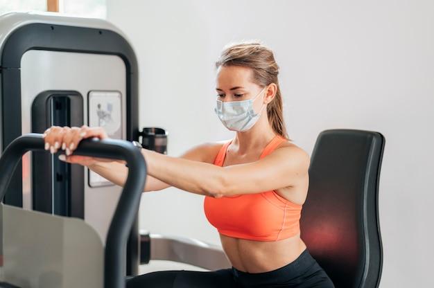 Donna con maschera allenandovi in palestra