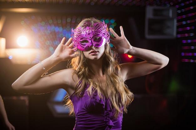 Woman with masquerade dancing on dance floor