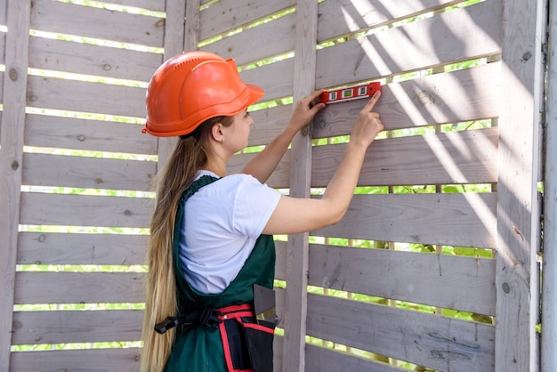 建設現場で水準器を持った女性。木製の壁を測定し、カメラのポーズをとる女性