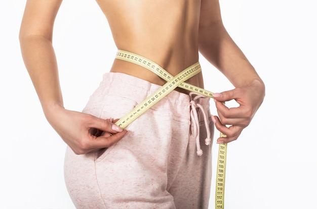 측정 테이프를 가진 여자입니다. 체중 감량 개념. 여자는 허리 스케일 테이프를 가지고 그녀의 얇은 허리를 보여줍니다.