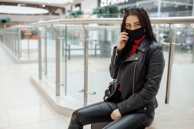 医療の黒いマスクとショッピングセンターでの携帯電話を持つ女性。コロナウイルスパンデミック。ショッピングセンターにマスクをした女性が立っています。防護マスクを着た女性がショッピングモールで買い物をしています。