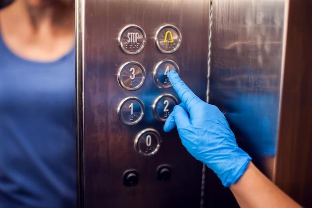 엘리베이터에서 버튼을 누르면 의료 장갑과 여자. 위생 및 건강 관리 개념