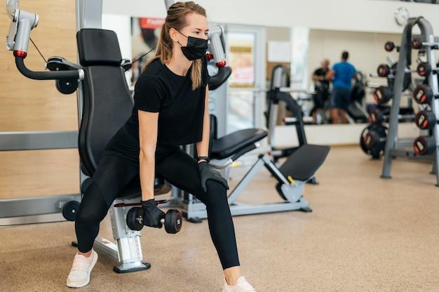 Женщина с медицинской маской и перчатками тренируется в тренажерном зале