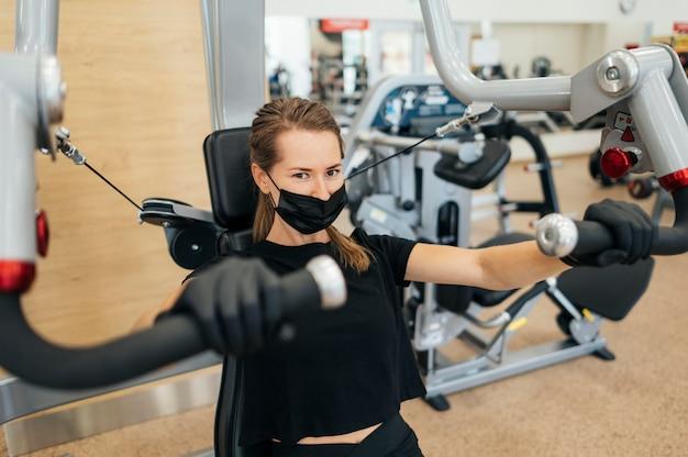 장비를 사용하는 체육관에서 의료 마스크와 장갑 훈련을 가진 여자