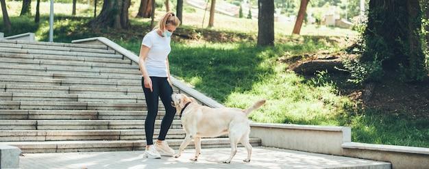 의료 마스크와 그녀의 골든 리트리버 공원에서 산책하는 여자