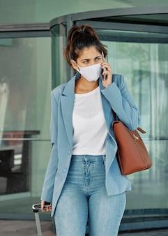 Женщина с медицинской маской и багажом разговаривает по смартфону в аэропорту во время пандемии