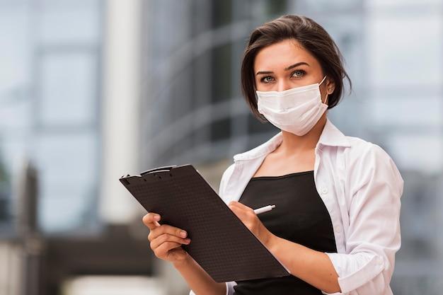 Женщина с медицинской маской и блокнотом позирует на открытом воздухе
