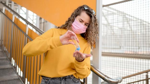 Женщина с медицинской маской и с помощью дезинфицирующего средства для рук
