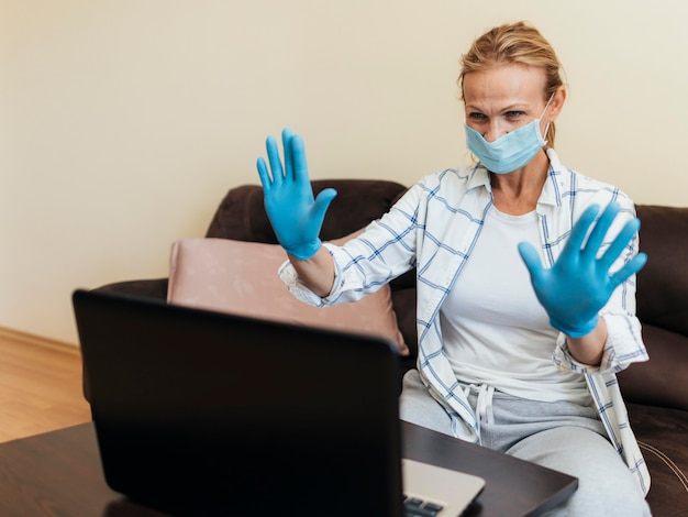Женщина с медицинской маской дома во время карантина работает на ноутбуке