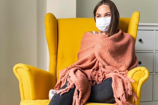 パンデミック時に肘掛け椅子で自宅で医療マスクを持つ女性