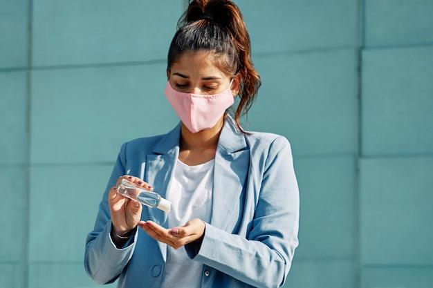유행병 동안 손 소독제를 사용하는 공항에서 의료 마스크를 가진 여자