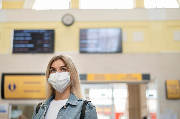 公共駅で医療用マスクを持った女性