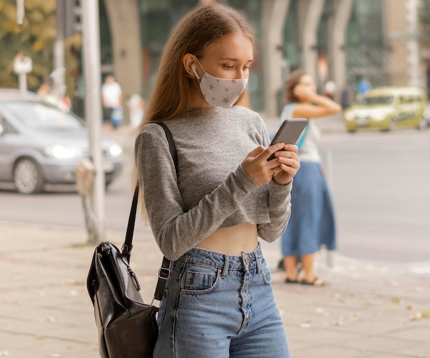 Woman with medical mask checking her phone