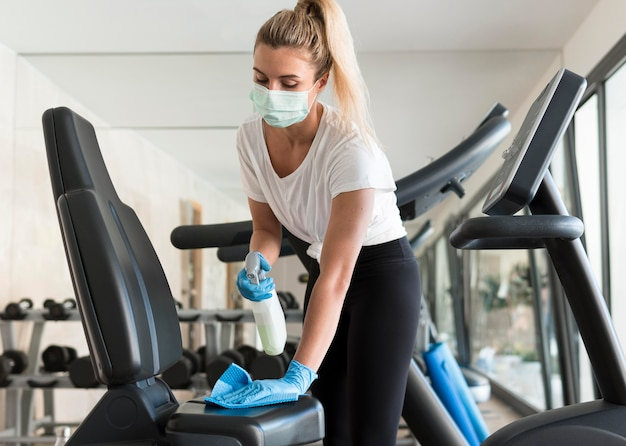 Woman with medical mask cleaning gym equipment