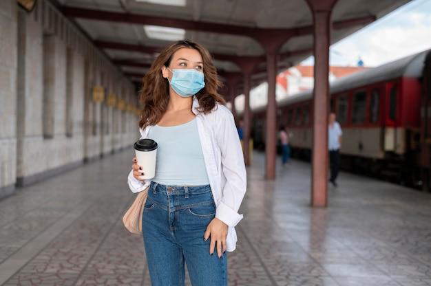 Donna con maschera medica e tazza di caffè alla stazione ferroviaria pubblica
