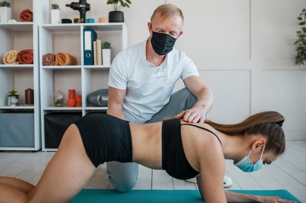 Donna con mascherina medica facendo esercizi in fisioterapia con fisioterapista maschio