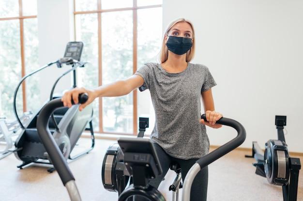 Женщина с медицинской маской во время пандемии тренируется в тренажерном зале
